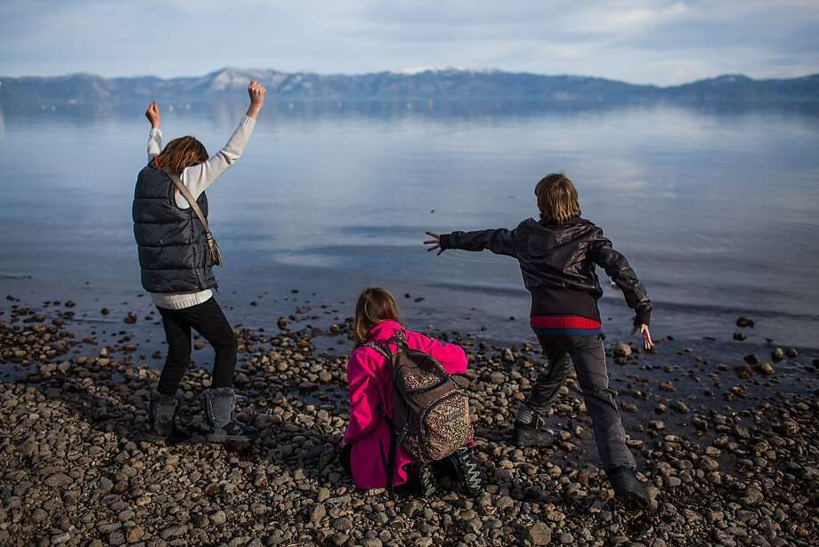 Alessandra Sutton, 10, of Novato (left), Samara Kincheloe-Owen, 12, of Colorado and Sam Sutton, 10, of Novato skip stones on the Lake Tahoe shore. Wintertime visitors have the chance to enjoy summertime activities while snow sports are on hold. Photo: Max Whittaker/Prime, Special To The Chronicle