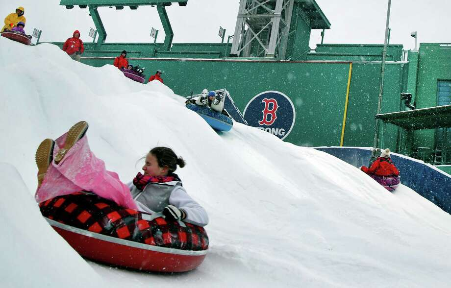 "Snow-tubers slide down the ""Monster Sled"" adjacent to Fenway Park's left field wall Thursday in Boston, where up to 14 inches of snow is forecast. Photo: Elise Amendola, STF / AP"