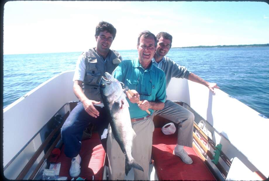 Vice President George H.W. Bush sits with his sons George W. and Jeb while holding a fish August 1983 in Kennebunkport, Maine. Photo: Cynthia Johnson, Getty Images