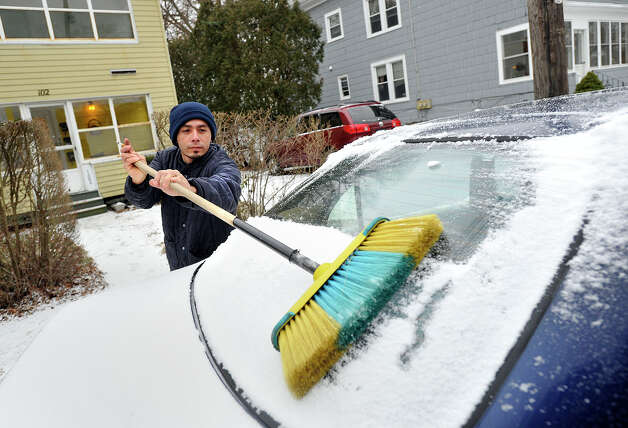 Geovani Barco uses a broom to clear snow from a car in Stamford, Conn., on Thursday, Jan. 2, 2014. Photo: Jason Rearick / Stamford Advocate