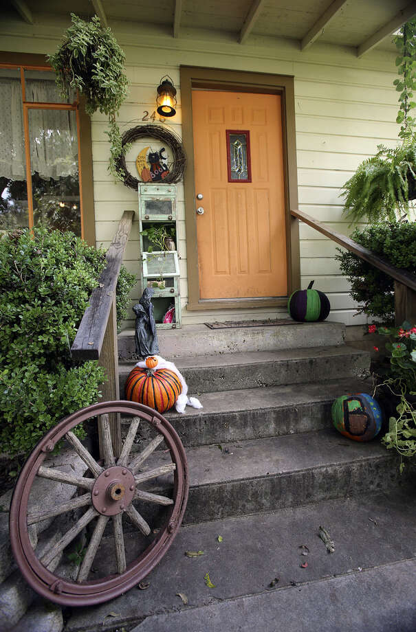 Melissa Hix decorated her doorstep with an old barber's cabinet and a wagon wheel. Color starts outside the small cottage. Photo: Photos By Tom Reel / San Anotnio Express-News