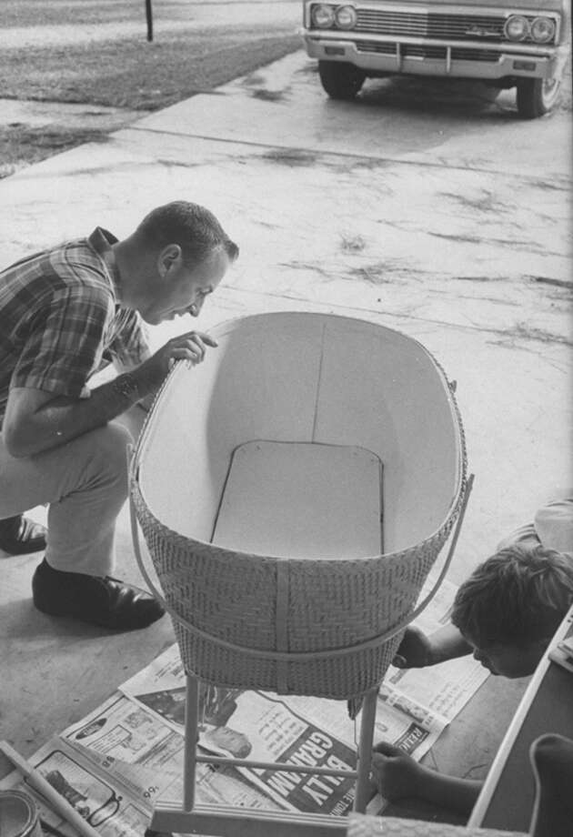 Astronaut Jim Lovell with his son Jay, 10, inspects an old bassinet they have just given a coat of paint in preparation of his expectant wife's baby while he is gone on Gemini 7 space flight. Photo: Ralph Morse, Time & Life Pictures/Getty Image / Time Life Pictures