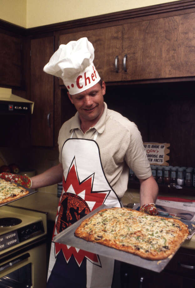 American astronaut Neil Armstrong, in an apron and hat labelled 'Chef' smiles as he uses oven mitts to up hold up a pair of pizzas in his Houston kitchen, March 1969. Photo: Ralph Morse, Time & Life Pictures/Getty Image / Time & Life Pictures