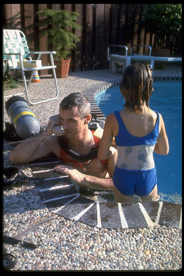 American astronaut Eugene Cernan takes a phone call from a Houston swimming pool in which he has been scuba diving, March 1969. On the right is his daughter Teresa. Photo: Ralph Morse, Time Life Pictures/Getty Images / The LIFE Picture Collection