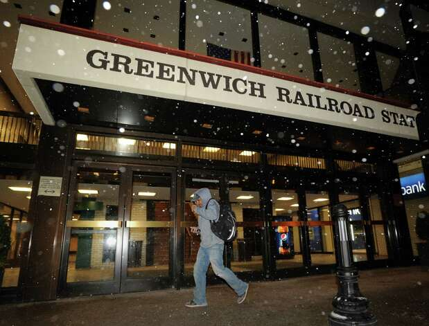 A man walks past the Greenwich Railroad Station as the snow starts falling on Railroad Avenue in Greenwich, Conn., Thursday night, Jan. 2, 2014. Photo: Bob Luckey / Greenwich Time