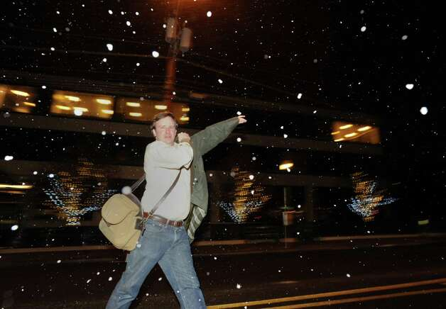 A man puts on a coat as the snow starts falling on Railroad Avenue in Greenwich, Conn., Thursday night, Jan. 2, 2014. Photo: Bob Luckey / Greenwich Time