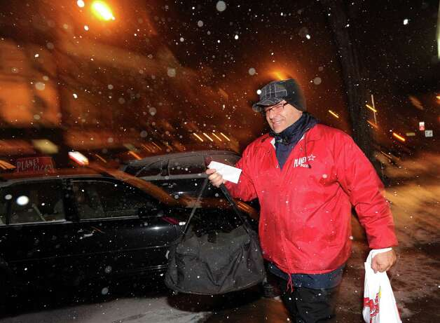 Planet Pizza deliveryman, Luiz Solrak, heads out on a delivery as the snow starts falling on Railroad Avenue in Greenwich, Conn., Thursday night, Jan. 2, 2014. Photo: Bob Luckey / Greenwich Time