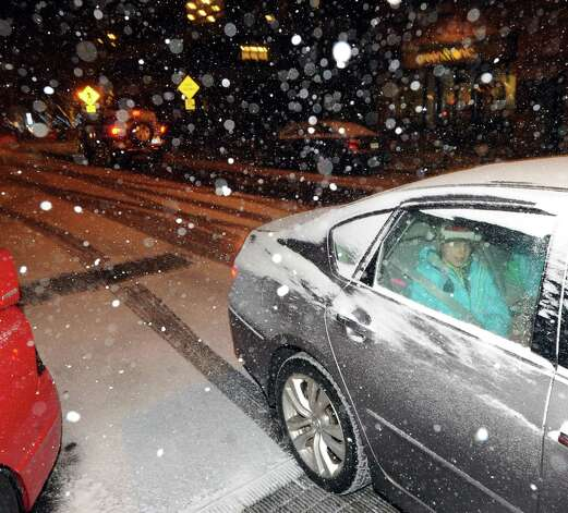 A passenger in a car looks out a window as the snow starts falling on Railroad Avenue in Greenwich, Conn., Thursday night, Jan. 2, 2014. Photo: Bob Luckey / Greenwich Time