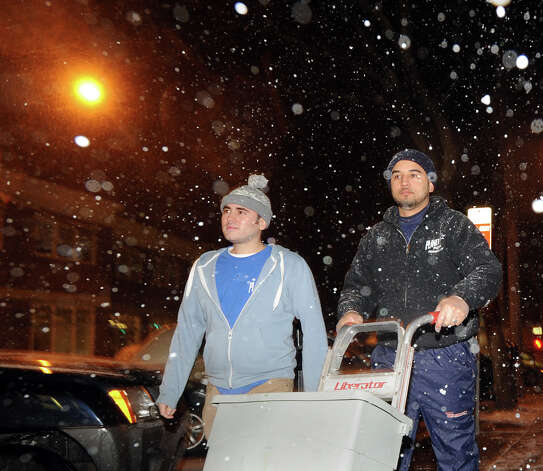 Peter Kyriakos, left, and Efran Felix, walk through the falling snow as they head to Planet Pizza where they work on Railroad Avenue in Greenwich, Conn., Thursday night, Jan. 2, 2014. Photo: Bob Luckey / Greenwich Time