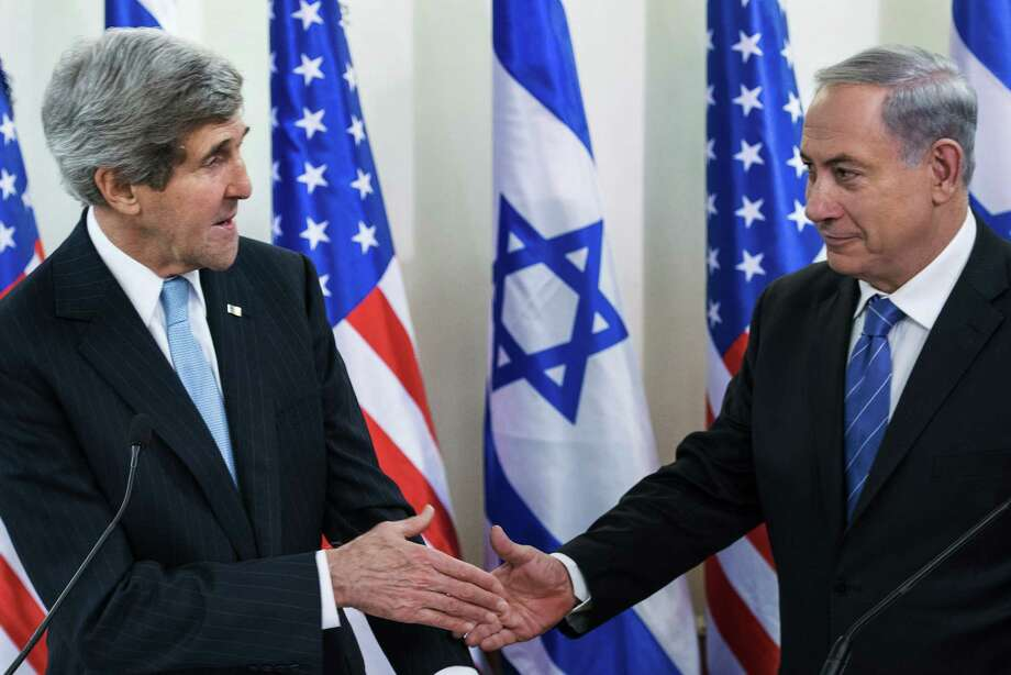 U.S. Secretary of State John Kerry, left, and Israeli Prime Minister Benjamin Netanyahu shake hands before a meeting at the prime minister's office in Jerusalem, Thursday, Jan. 2, 2014. Kerry arrived Thursday in Israel to broker Mideast peace talks that are entering a difficult phase aimed at reaching a two-state solution between the Israelis and Palestinians. (AP Photo/Brendan Smialowski, Pool) Photo: Brendan Smialowski, POOL / POOL AFP