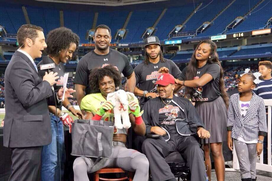 Surrounded by members of his family, Ozen cornerback Tony Brown holds up a Alabama Crimson Tide stuffed elephant after he had verbally committed to the national power during Thursday's Under Armour All-America Game. -- Photo provided by Tammy Walker-Brown