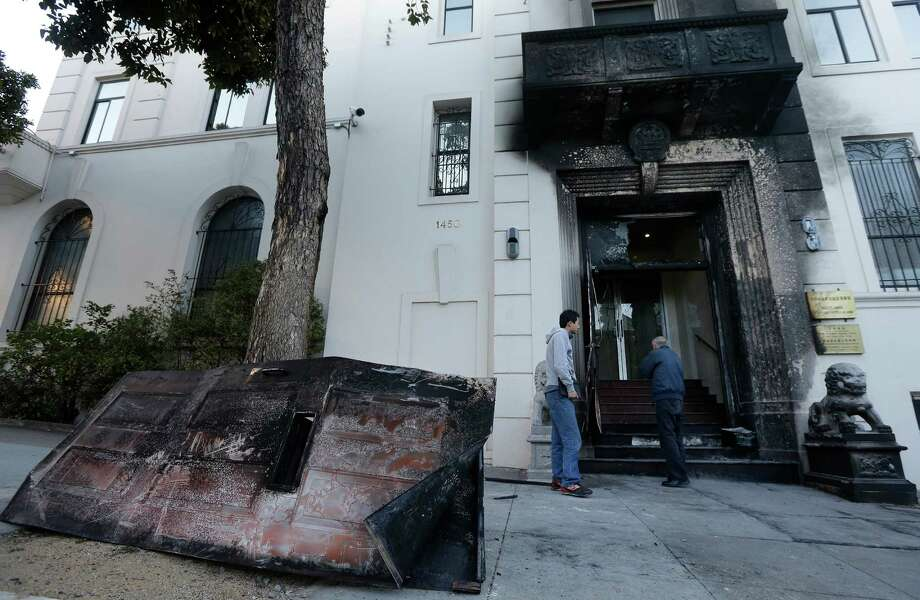 Two men inspect the fire damage done to the entrance of the Chinese Consulate in San Francisco. The consulate said in a notice on its website that a person came out of a van parked outside the compound Wednesday night with two buckets of gasoline, poured the fuel on the front of the consulate building and set it on fire. (AP Photo/Jeff Chiu) Photo: Jeff Chiu, STF / AP