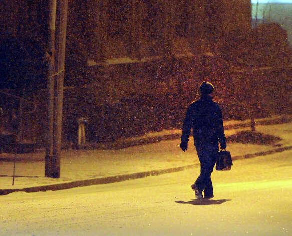 A man walks along West Elm Street during the snow storm that hit Greenwich, Conn., Thursday night, Jan. 2, 2014. Photo: Bob Luckey / Greenwich Time