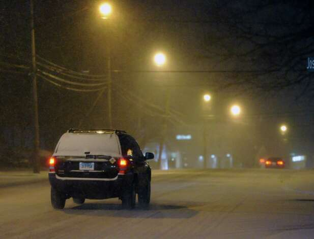 A vehicle drives on West Putnam Avenue during the snow storm that hit Greenwich, Conn., Thursday night, Jan. 2, 2014. Photo: Bob Luckey / Greenwich Time