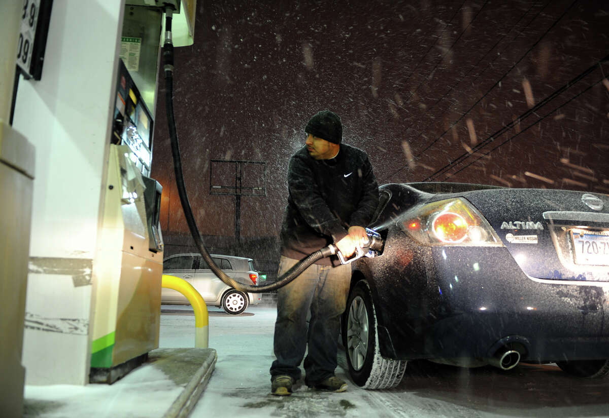 Diego Lopez, of Bridgeport, fills up at H&A Convenience on Fairfield Avenue during the start of a major snow storm in Bridgeport, Conn. on Thursday January 2, 2014.