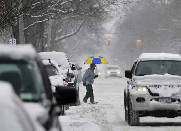 A man with an umbrella looks to cross over Madison Ave. as snow falls on Thursday, Jan. 2, 2014 in Albany, NY.     (Paul Buckowski / Times Union) Photo: PAUL BUCKOWSKI / 00025207A
