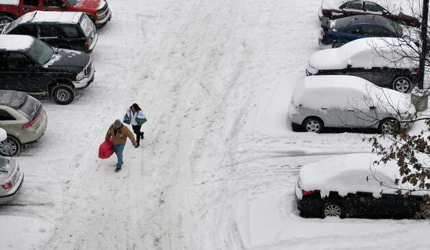 Travelers make their way through the parking lot on their way towards the terminal at the Albany International Airport on Thursday, Jan. 2, 2014, in Colonie, N.Y. (Paul Buckowski / Times Union) Photo: PAUL BUCKOWSKI / 00025207A