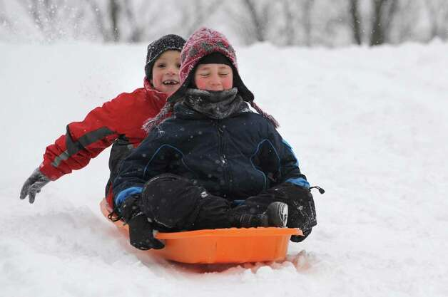 Guilderland buddies Noah Johnson, 6, left, and Quinn Helfrich, 7, enjoy the new snow by sledding on the Tawasentha winter recreation area hill on Thursday, Jan. 2, 2014 in Guilderland, N.Y. (Lori Van Buren / Times Union) Photo: Lori Van Buren / 00025207A