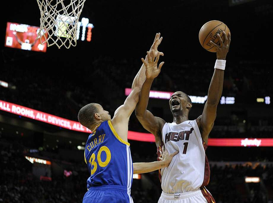 Miami Heat forward Chris Bosh shoots over Golden State Warriors guard Stephen Curry during the first half at AmericanAirlines Arena in Miami on Thursday, Jan. 2, 2014. (Michael Laughlin/Sun Sentinel/MCT) Photo: Michael Laughlin, McClatchy-Tribune News Service