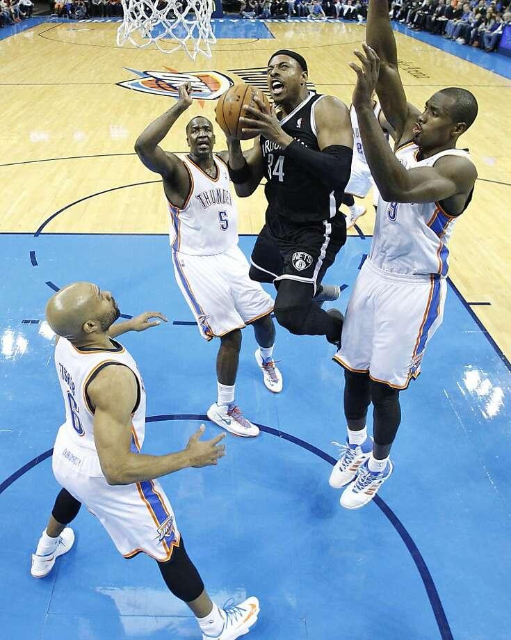 The Nets' Paul Pierce floats past Derek Fisher (left), Kendrick Perkins and Serge Ibaka. Photo: Sue Ogrocki, Associated Press