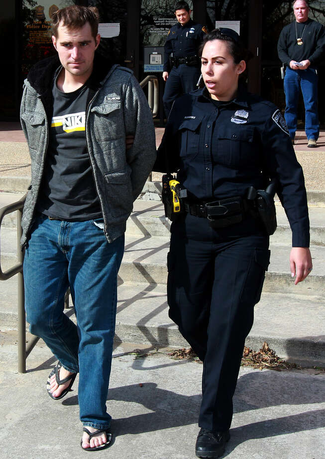 After his arrest Thursday, multiple- robbery suspect Curtis Joseph Wisniewski is escorted to a police car by a San Antonio police officer. Photo: John Davenport / San Antonio Express-News / ©San Antonio Express-News/Photo may be sold to the public