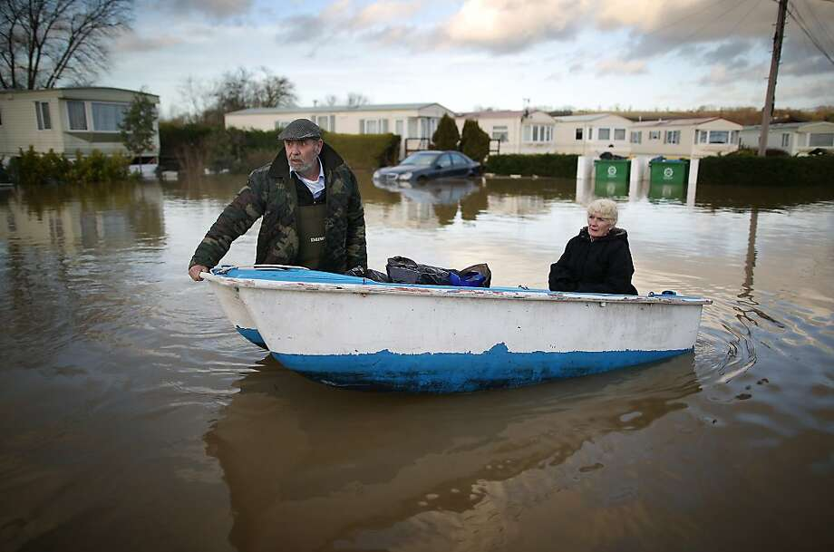 YALDING, ENGLAND - JANUARY 02:  Ian Peacock pulls a boat carrying fellow resident Caroline Hine as they rescue possesions from flooded caravans at the Little Venice Country Park on January 2, 2014 in Yalding, England. Government ministers are holding a COBRA emergency committee meeting today to discuss the United Kingdom's response to recent flooding.  (Photo by Peter Macdiarmid/Getty Images) *** BESTPIX *** Photo: Peter Macdiarmid, Getty Images