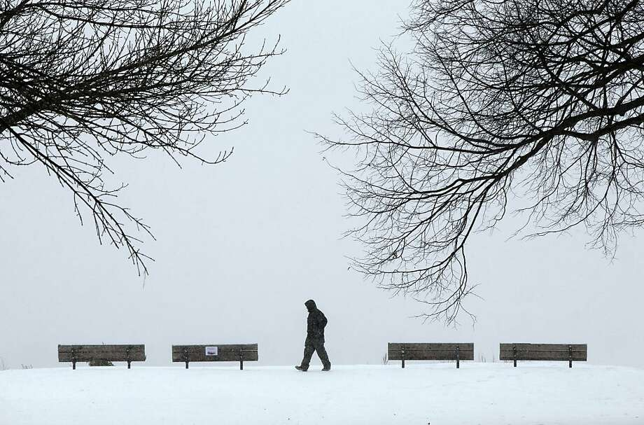 "Daryl Santos, 27, of Los Angeles, Calif., walks through a park while experiencing a snowstorm, Thursday, Jan. 2, 2014,  inPortland, Maine. White-out conditions and a temperature of 0 degrees F greeted Santos on his first trip to the East Coast. Compared to southern California, 'it's an intense change,"" he said.  (AP Photo/Robert F. Bukaty) Photo: Robert F. Bukaty, Associated Press"