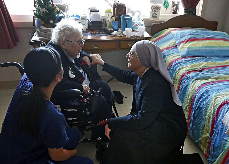 Mother Patricia Mary, right, and nurse Friary Nguyen visit 99-year-old resident Helen Reichenbach in her room at the Mullen Home for the Aged, run by Little Sisters of the Poor, in Denver, Thursday Jan. 2, 2014. Acting at the request of Little Sisters of the Poor, Justice Sonia Sotomayor on Tuesday Dec. 31, 2013, temporarily blocked the Obama administration from forcing some religious-affiliated groups to provide health insurance coverage of birth control or face penalties as part of the Affordable Care Act. The stay was issued just hours before the requirement was to go into effect on New Year's Day. (AP Photo/Brennan Linsley) Photo: Brennan Linsley, Associated Press