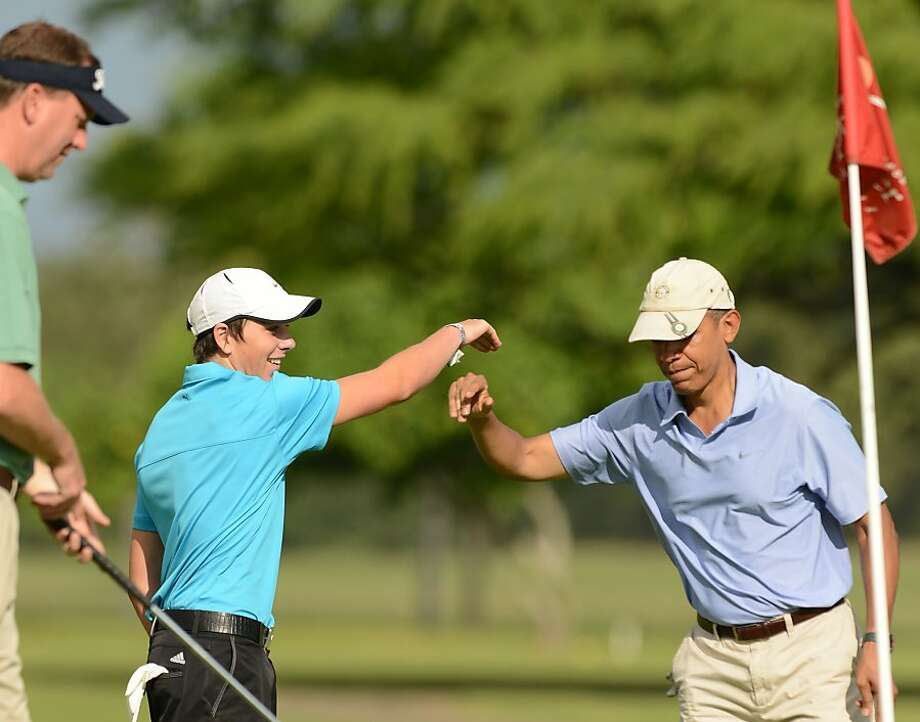 KANEOHE, HI - JANUARY 2:  U.S. President Barack Obama (R) fist bumps the Prime Minister of New Zealand's son Max Key (C) on the second green at  Marine Corps Base Hawaii's Kaneohe Klipper Golf Course January 2, 2014 in Kaneohe, Hawaii. The Obama family is in Hawaii for the winter holidays.  (Photo by Cory Lum-Pool/Getty Images) Photo: Pool, Getty Images