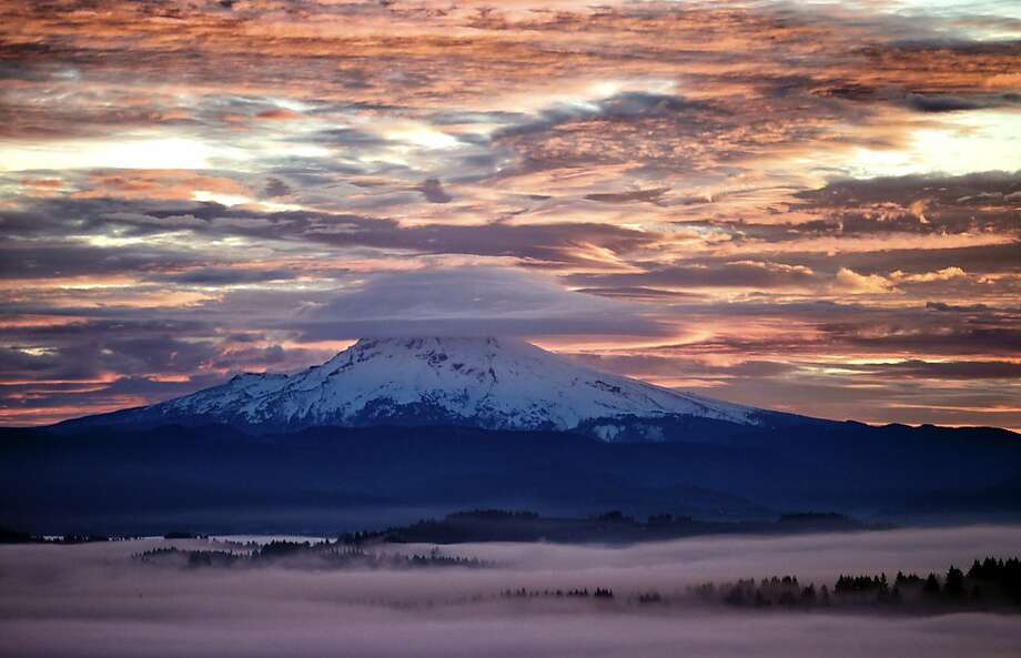 Fog settles low over Happy Valley as a lenticular cloud obscures the summit of Mount Hood as the sunrise lights up wispy clouds, Thursday, Jan. 2, 2014, in a view looking north from Mount Scott, Ore. (AP Photo/The Oregonian, Thomas Boyd)  MAGS OUT; TV OUT; LOCAL TV OUT; LOCAL INTERNET OUT; THE MERCURY OUT; WILLAMETTE WEEK OUT; PAMPLIN MEDIA GROUP OUT Photo: Thomas Boyd, Associated Press