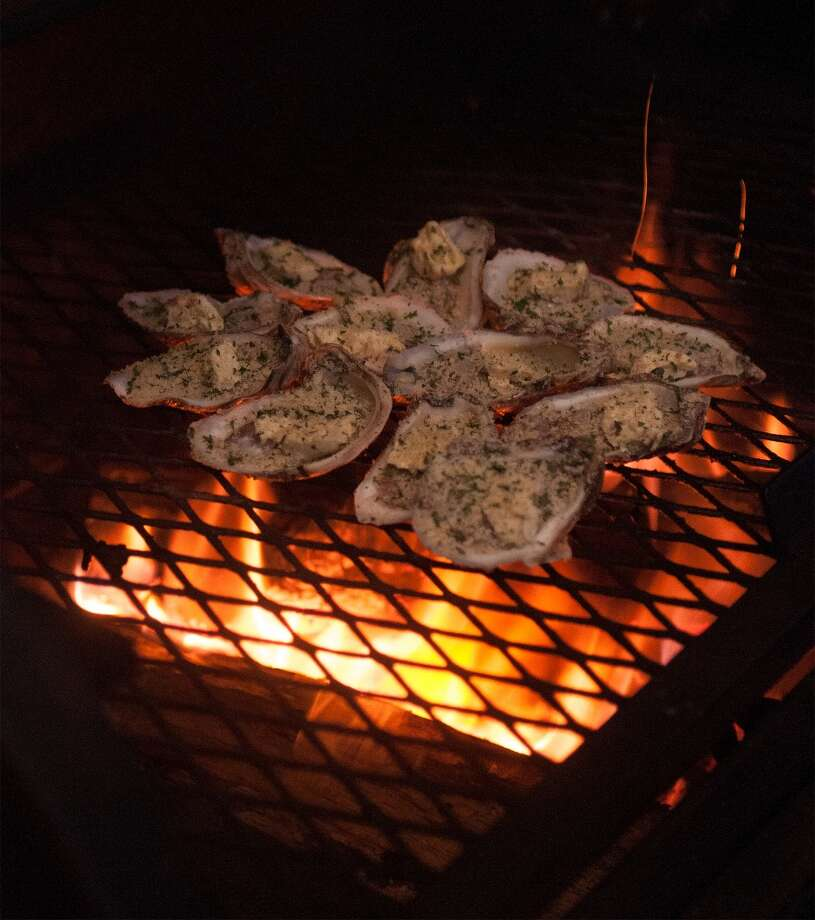 Oysters on the shell over the fire at Stingaree on Bolivar Penisula. Photo by Joe Winston/cat5