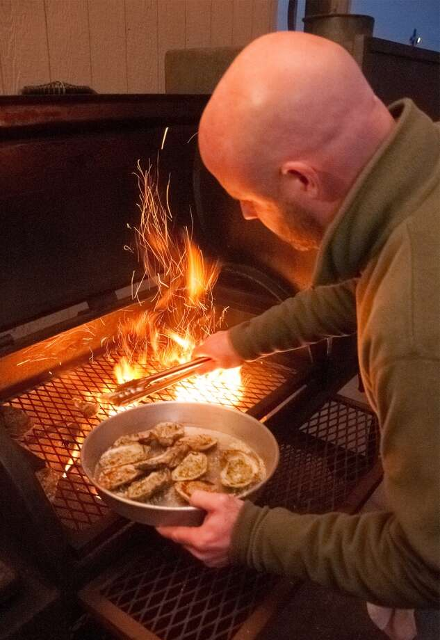 Brad Vratis, Owner of Stingaree places oysters on a wood fired grill at the Bolivar Peninsula restaurant on Friday night. Photo by Joe Winston/cat5