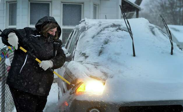 Carol Coelho clears the snow from her car early Friday morning on Mountainville Ave. in Danbury, Conn.,  Jan. 3, 2013. , so she could get to her job at a doctor's office. Photo: Carol Kaliff / The News-Times