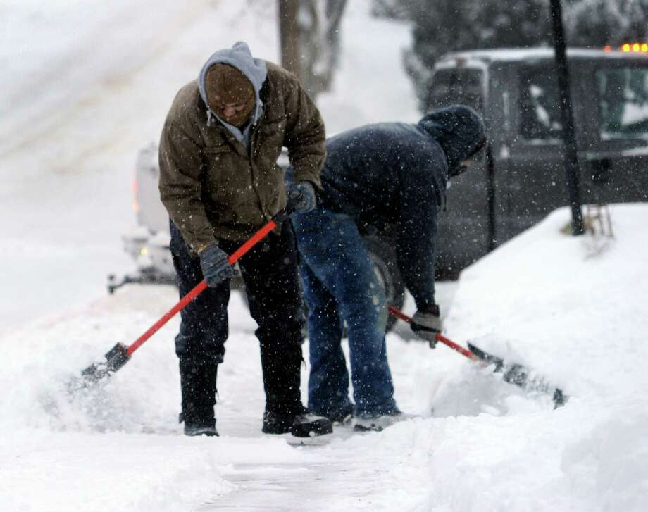 Workers shovel the sidewalks on Seeley Street in Danbury early Friday morning after an over night snow fall, Jan. 3, 2013. Photo: Carol Kaliff / The News-Times