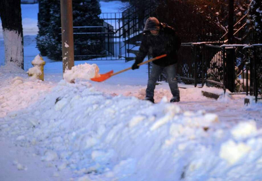 A worker shovels the snow from a sidewalk on Liberty Street in Danbury, Conn. Friday, Jan. 3, 2013. Photo: Carol Kaliff / The News-Times
