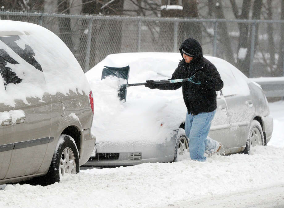 A man clears snow from his car during the snow storm that hit Greenwich, Conn., Friday morning, Jan. 3, 2014. Photo: Bob Luckey / Greenwich Time