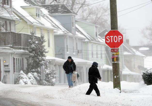 People walk on North Water Street as seen during the snow storm that hit Greenwich, Conn., Friday morning, Jan. 3, 2014. Photo: Bob Luckey / Greenwich Time