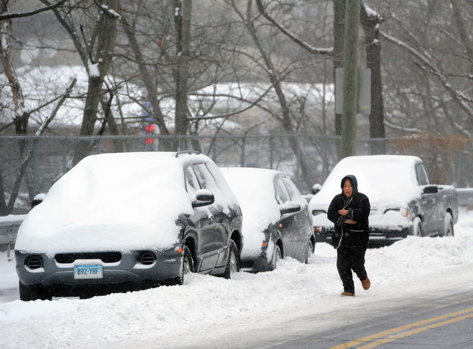 A woman walks along a snow-covered Byram Road during the snow storm that hit Greenwich, Conn., Friday morning, Jan. 3, 2014. Photo: Bob Luckey / Greenwich Time