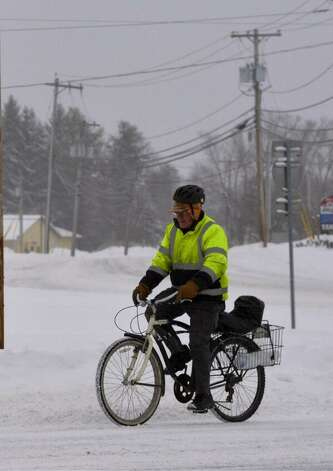 This intrepid traveler might have the right idea - a mountain bike, to get through the snow in Halfmoon on Friday. (Skip Dickstein / Times Union)