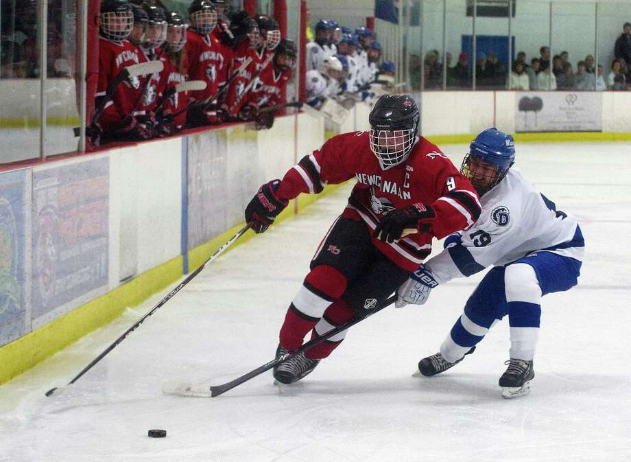 New Canaan's Peter Reinhardt, left, and Darien's Robbie Juterbock, rigth, compete for control of the puck during Saturday's boys hockey game at the Darien Ice Rink in Darien, Conn., on December 28, 2013. Photo: Lindsay Perry / Stamford Advocate