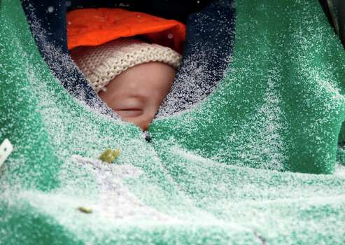 Two-month-old Jack Hsi takes a nap sheltered in his baby carrier while snow falls in Boston, Thursday, Jan. 2, 2014. Up to 14 inches of snow is forecast for the Boston area. Photo: Elise Amendola, AP / AP