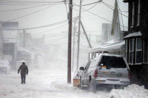 A man walks in the snow down a road along the shore in Scituate, Mass., Friday, Jan. 3, 2014. A winter storm slammed into the U.S. Northeast with howling winds and frigid cold, dumping nearly 2 feet (60 centimeters) of snow in some parts and whipping up blizzard-like conditions Friday. Photo: Michael Dwyer, ASSOCIATED PRESS / AP2014