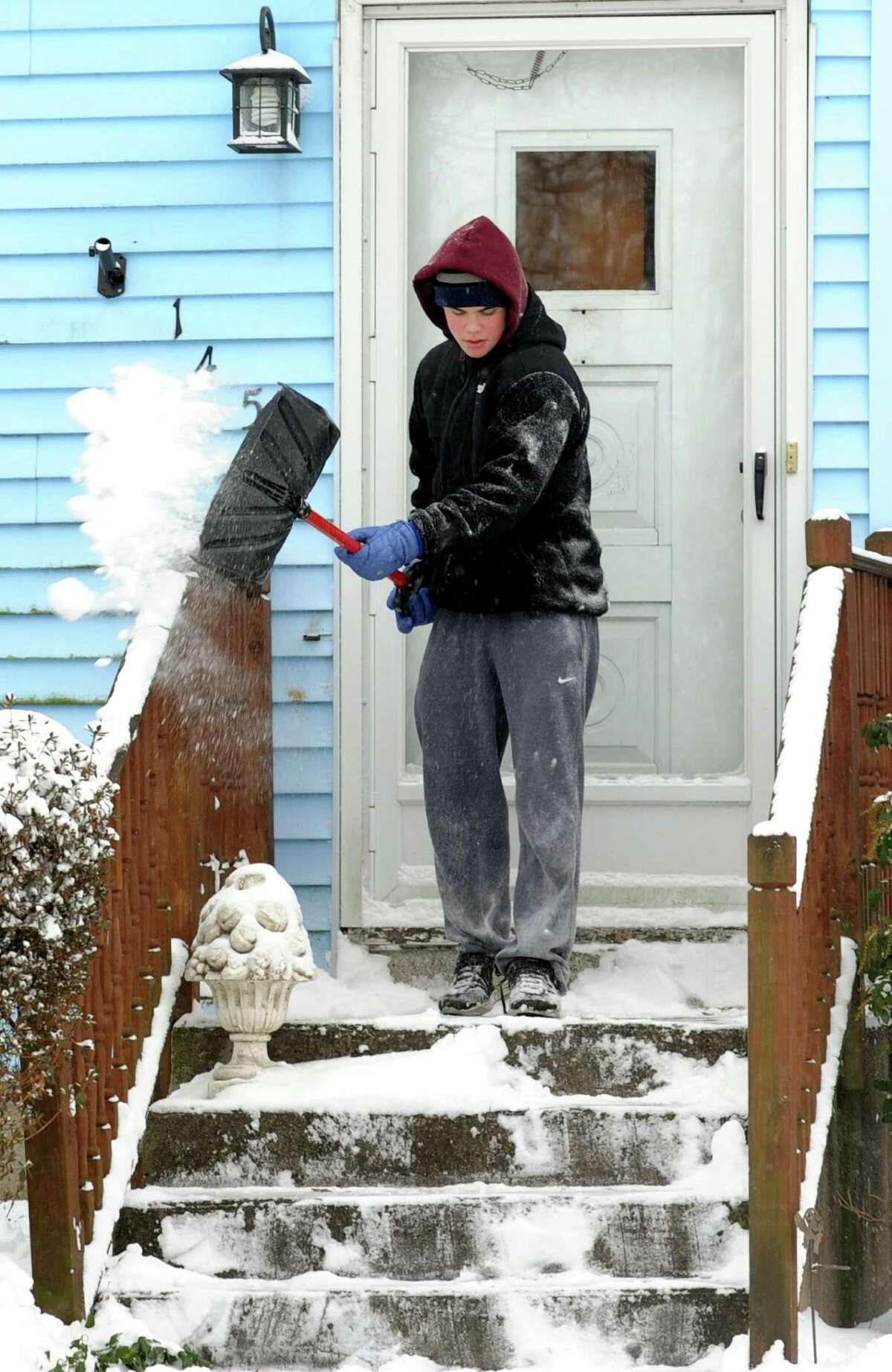 Devin Thomas clears the front porch of his Tuckahoe Lane home in Fairfield, Conn. on Friday, Jan. 3, 2014. An overnight storm dumped about 6 inches of snow in the area.
