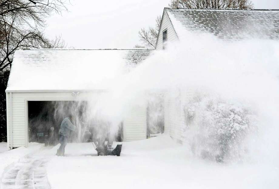 Barely visible through the blowing snow, a resident starts to dig out after an overnight snow storm in Fairfield, Conn. on Friday, Jan. 3, 2014. Photo: Cathy Zuraw / Connecticut Post