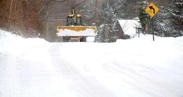 A backhoe loader makes it's way down Reid Street in Fairfield, Conn. on Friday, Jan. 3, 2014. About 6 inches of snow fell in the area overnight. Photo: Cathy Zuraw / Connecticut Post