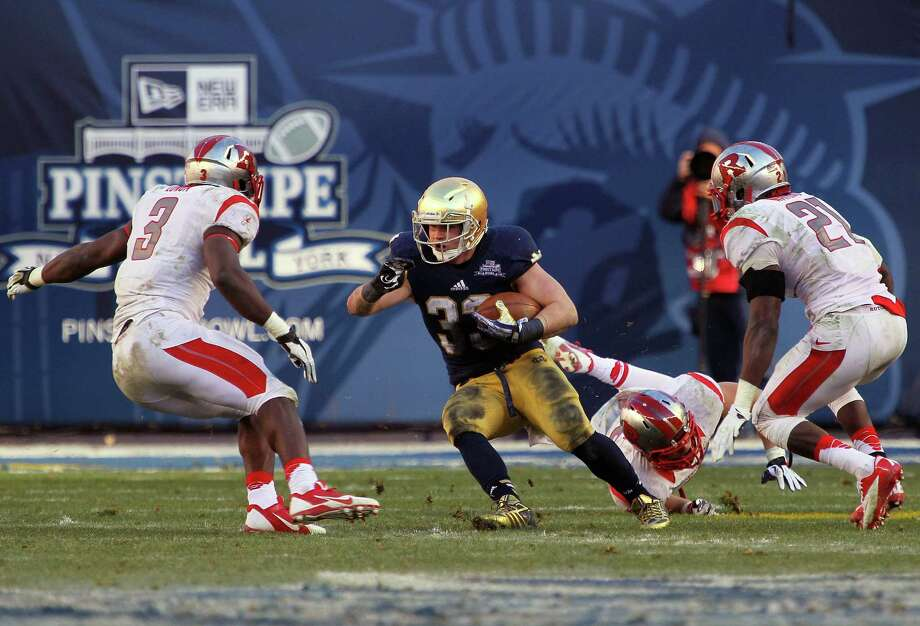 Cam McDaniel #33 of the Notre Dame Fighting Irish runs the ball against Steve Longa #3, Lorenzo Waters #21 and Kevin Snyder #45 of the Rutgers Scarlet Knights during the New Era Pinstripe Bowl at Yankee Stadium on December 28, 2013 in the Bronx Borough of New York City. Photo: Nate Shron, Getty Images / 2013 Nate Shron