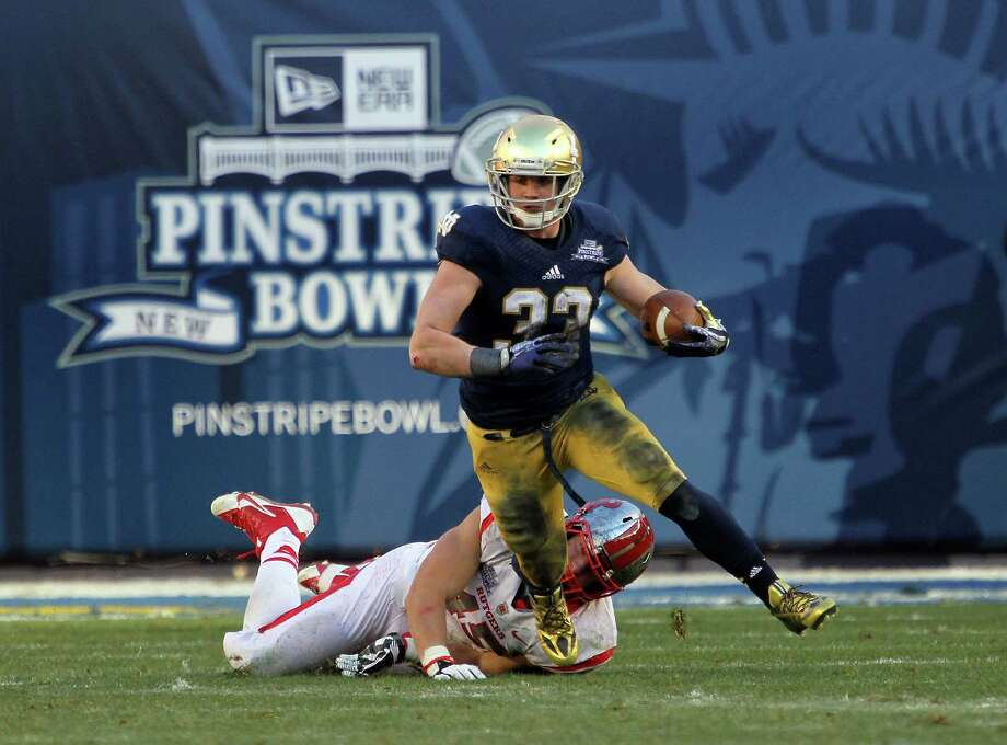 Cam McDaniel #33 of the Notre Dame Fighting Irish runs the ball against Kevin Snyder #45 of the Rutgers Scarlet Knights during the New Era Pinstripe Bowl at Yankee Stadium on December 28, 2013 in the Bronx Borough of New York City. Photo: Nate Shron, Getty Images / 2013 Nate Shron