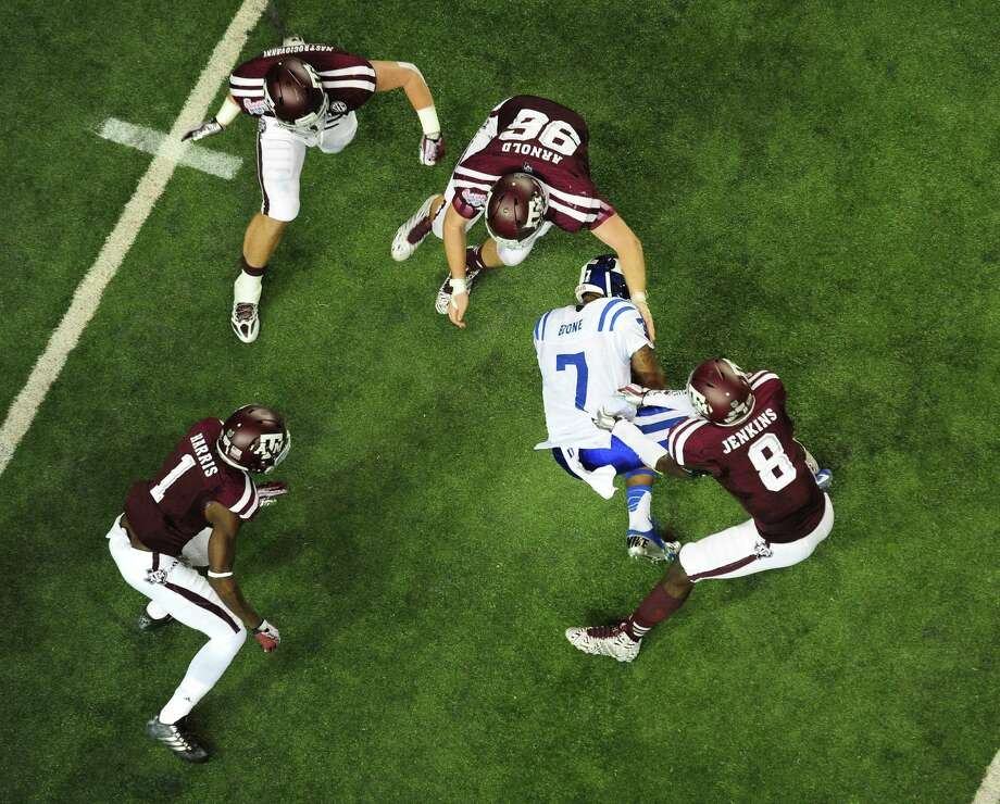 Anthony Boone #7 of the Duke Blue Devils is tackled by Steven Jenkins #8 and Jay Arnold #96 of the Texas A&M Aggies during the Chick-Fil-A Bowl at the Georgia Dome on December 31, 2013 in Atlanta, Georgia. Texas A&M defeated Duke 52-48. Photo: Scott Cunningham, Getty Images / 2013 Scott Cunningham
