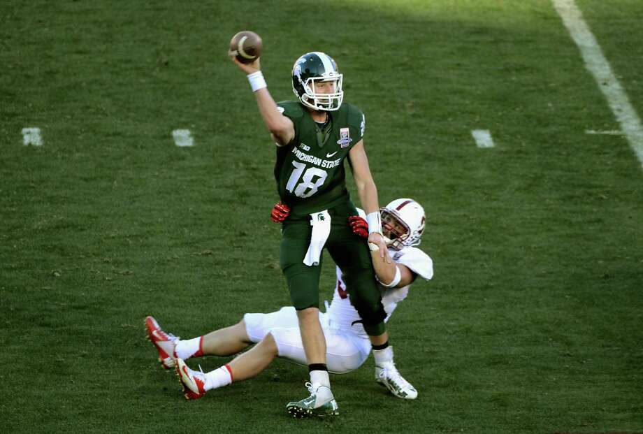 Quarterback Connor Cook #18 of the Michigan State Spartans his hit as he throws during the 100th Rose Bowl Game presented by Vizio against the Stanford Cardinal at the Rose Bowl on January 1, 2014 in Pasadena, California. Photo: Jonathan Moore, Getty Images / 2014 Getty Images