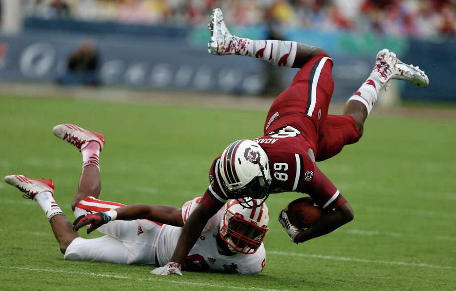 Jerell Adams #89 of the South Carolina Gamecocks gets tackled by Sojourn Shelton #8 of the Wisconsin Badgers during the first half of the Capital One Bowl on January 1, 2014 in Orlando, Florida. Photo: Scott Halleran, Getty Images / 2014 Getty Images